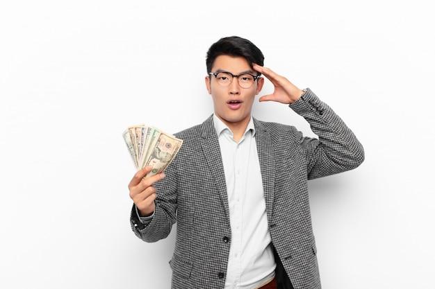 Junger japanischer mann, der glücklich, erstaunt und überrascht aussieht, lächelt und erstaunliche und unglaubliche gute nachrichten realisiert. geldkonzept