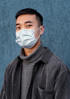 Junger japanischer mann, der maske trägt