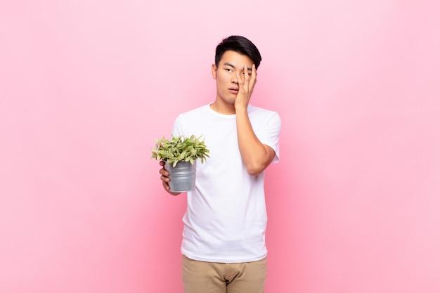 Junger japanischer mann, der sich nach einer ermüdenden, langweiligen und mühsamen aufgabe gelangweilt, frustriert und schläfrig fühlt und gesicht mit hand hält, die eine pflanze hält