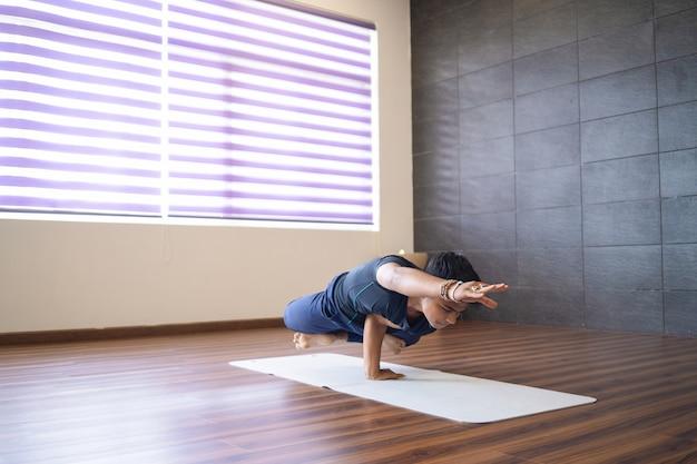 Junger jogi, der eine handstandhaltung in der turnhalle tut