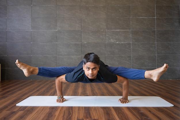 Junger jogi, der leuchtkäferhaltung tut und in der turnhalle balanciert