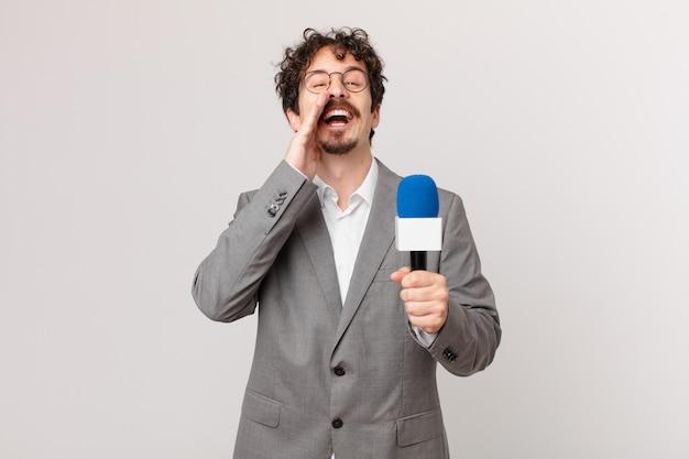 Junger journalist, der sich glücklich fühlt und mit den händen neben dem mund einen großen schrei ausspricht