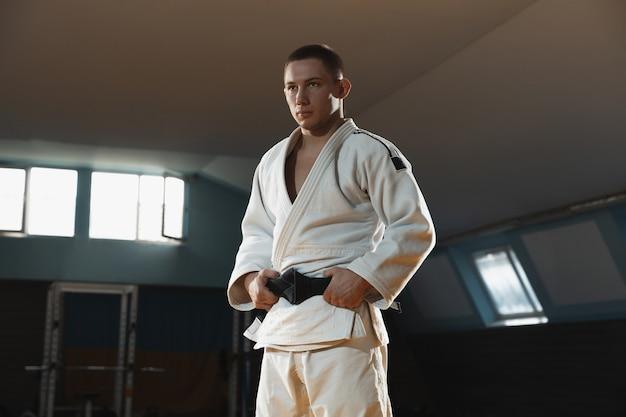 Junger judokämpfer im kimono, der bequem in der turnhalle stark und gesund aufwirft