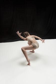 Junger jugendlich tänzer auf weißem boden.