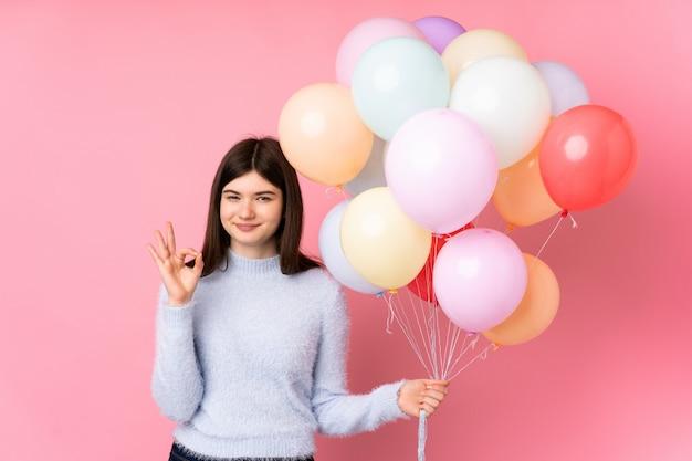 Junger jugendlicher, der viele ballone zeigen ein okayzeichen mit den fingern hält