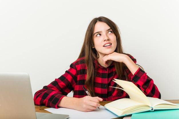 Junger jugendlicher, der zurück zu ihrer routine erledigt hausaufgaben geht.