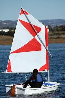 Junger jugendlichkapitän, der ein kleines segelboot steuert.