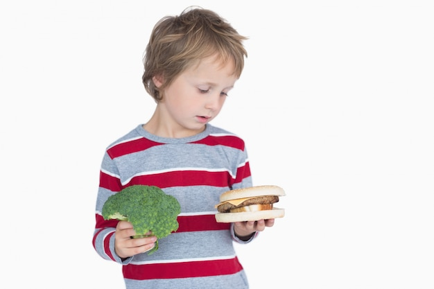 Junger junge, der brokkoli und burger hält