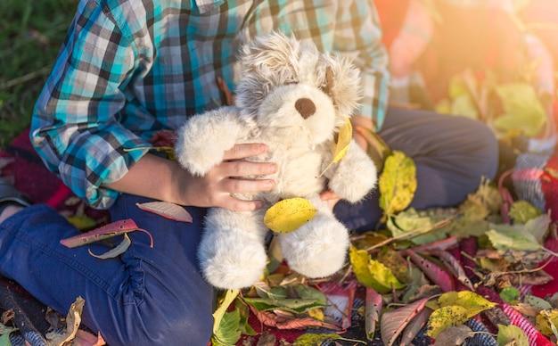 Junger junge, der einen netten teddybären anhält