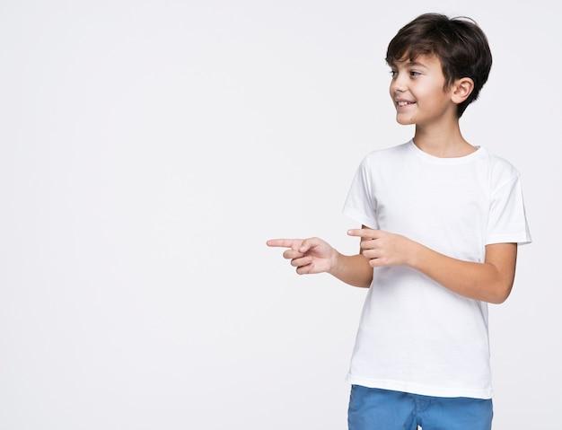 Junger junge, der mit exemplarplatz zeigt