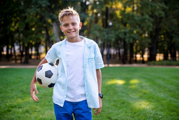 Junger junge mit der fußballkugel, die kamera betrachtet