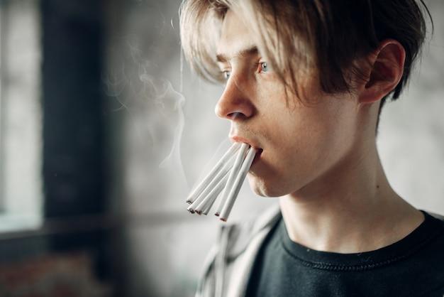 Junger junkie mit vielen zigaretten im mund