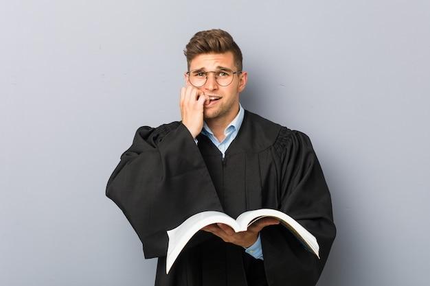 Junger jurist, der ein buch hält, das die fingernägel beißt, nervös und sehr besorgt.
