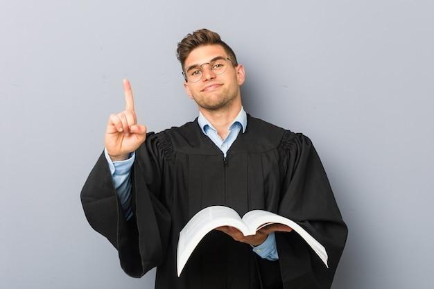 Junger jurist, der ein buch hält, das nummer eins mit dem finger zeigt.