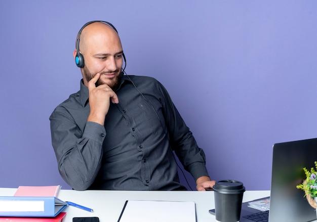 Junger kahler callcenter-mann, der headset am schreibtisch mit arbeitswerkzeugen lokalisiert auf lila hintergrund trägt