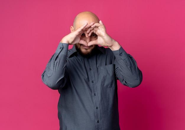 Junger kahler callcenter-mann, der herzzeichen tut und durch finger auf kamera lokalisiert auf purpurrotem hintergrund mit kopienraum schaut