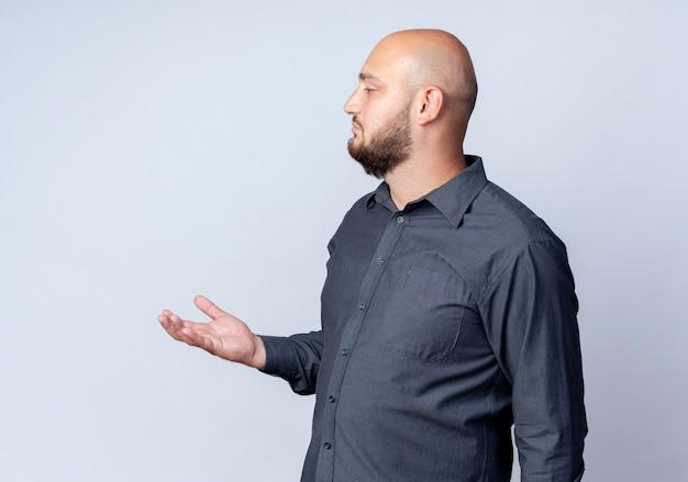 Junger kahler callcenter-mann, der in der profilansicht steht, die leere hand zeigt und gerade lokalisiert auf weißem hintergrund schaut
