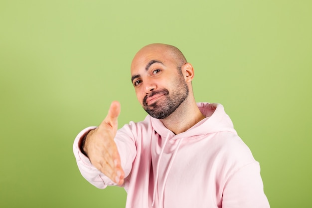 Junger kahler kaukasischer mann im rosa kapuzenpulli lokalisiert, freundlich, das händedruck als begrüßung und begrüßung anbietet
