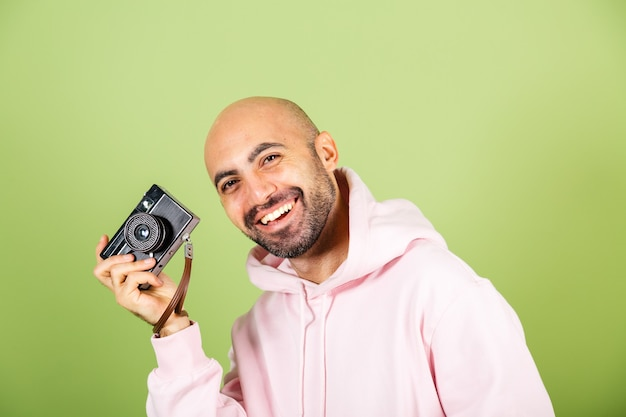 Junger kahler kaukasischer mann im rosa kapuzenpulli lokalisiert, positive hipster halten kamera
