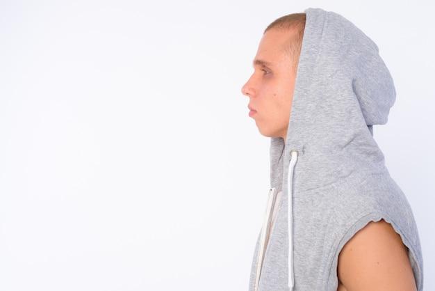 Junger kahler rebellischer mann, der kapuzenhemd trägt, das gegen weiße wand lokalisiert wird