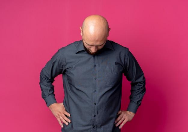 Junger kahlköpfiger callcenter-mann, der hände auf taille setzt, die lokal auf purpurrotem hintergrund mit kopienraum schaut