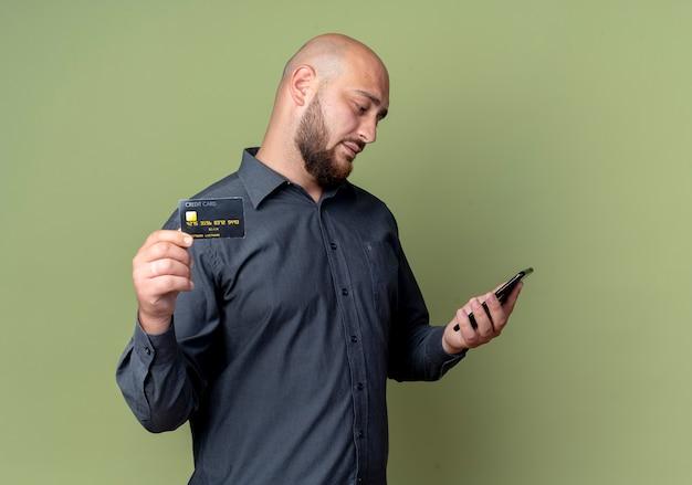 Junger kahlköpfiger callcenter-mann, der handy hält und betrachtet und kreditkarte an der kamera lokalisiert auf olivgrünem hintergrund mit kopienraum zeigt