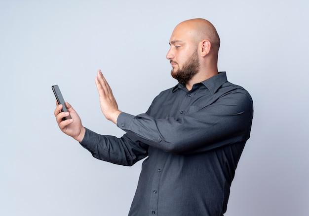 Junger kahlköpfiger callcenter-mann, der handy hält und betrachtet und nicht lokalisiert auf weißem hintergrund gestikuliert