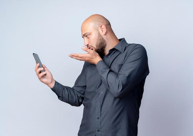 Junger kahlköpfiger callcenter-mann, der handy hält und betrachtet und schlagkuss lokalisiert auf weißem hintergrund mit kopienraum sendet