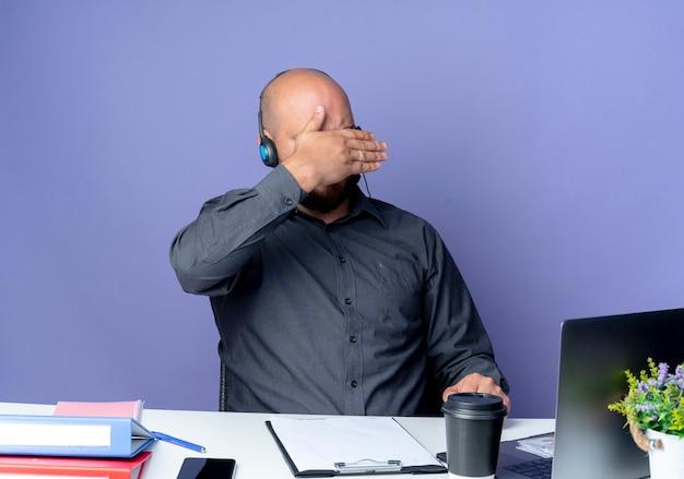 Junger kahlköpfiger callcenter-mann, der headset sitzt am schreibtisch mit arbeitswerkzeugen abdeckt gesicht mit hand lokalisiert auf lila hintergrund