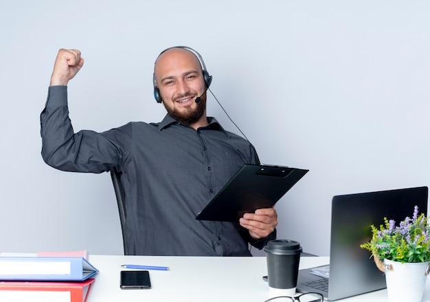 Junger kahlköpfiger callcenter-mann, der headset sitzt am schreibtisch mit arbeitswerkzeugen hält zwischenablage lokalisiert auf weißem hintergrund