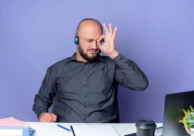 Junger kahlköpfiger callcenter-mann, der headset sitzt am schreibtisch mit arbeitswerkzeugen tut blickgeste auf laptop lokalisiert auf lila hintergrund