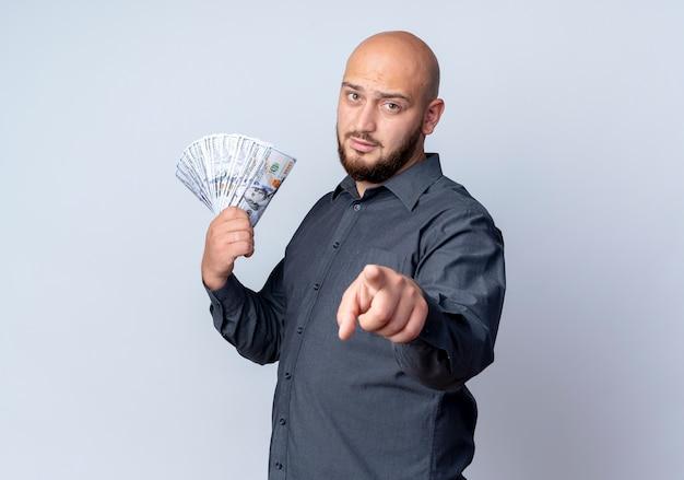 Junger kahlköpfiger callcenter-mann, der in der profilansicht steht, die geld lokalisiert auf weißem hintergrund mit kopienraum hält