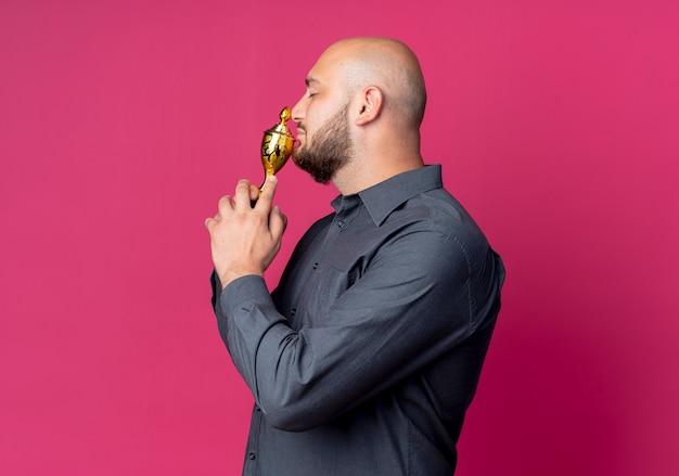 Junger kahlköpfiger callcenter-mann, der in der profilansicht steht und gewinnerpokal nahe mund mit geschlossenen augen auf purpurrotem hintergrund mit kopienraum isoliert hält