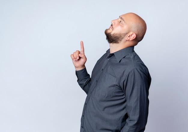 Junger kahlköpfiger callcenter-mann, der in der profilansicht steht und lokalisiert auf weißem hintergrund mit kopienraum schaut