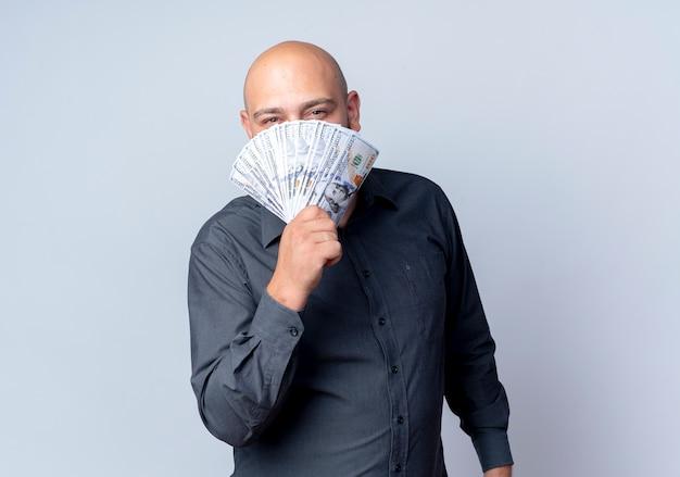 Junger kahlköpfiger callcenter-mann, der kamera von hinter geld lokalisiert auf weißem hintergrund mit kopienraum betrachtet