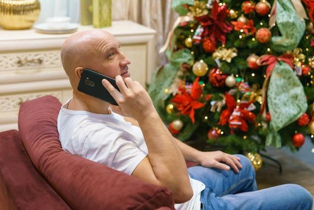 Junger kahlköpfiger glücklicher mann sitzt vor geschmücktem weihnachtsbaum in seiner wohnung und telefoniert...