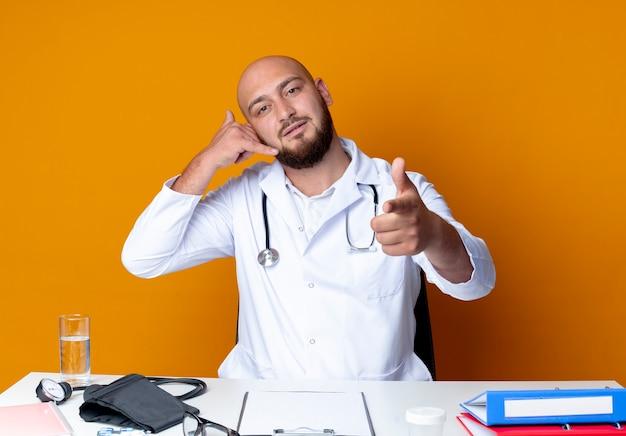 Junger kahlköpfiger männlicher arzt, der medizinische robe und stethoskop trägt, die am schreibtisch mit medizinischen werkzeugen sitzen, die telefonanrufgeste zeigen und auf kamera auf orange zeigen