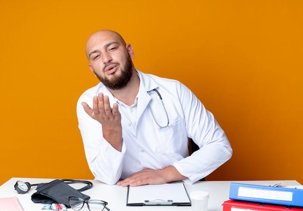 Junger kahlköpfiger männlicher arzt, der medizinisches gewand und stethoskop trägt, der am schreibtisch sitzt