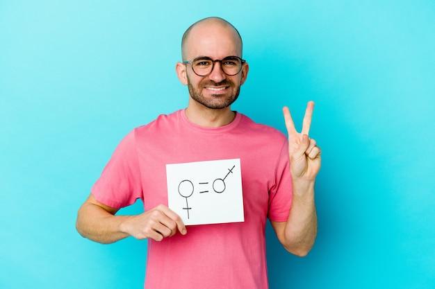 Junger kahlköpfiger mann, der ein gleichheitsgeschlechtsplakat lokalisiert auf gelber wand hält, die nummer zwei mit den fingern zeigt