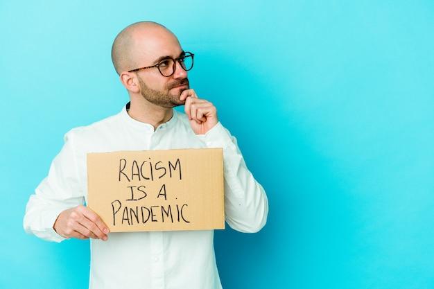 Junger kahlköpfiger mann, der einen rassismus hält, ist eine pandemie, die auf weißer wand isoliert ist, die mit zweifelhaftem und skeptischem ausdruck seitwärts schaut
