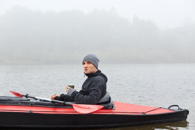 Junger kajakfahrer, der im kanu in der mitte des flusses oder des sees sitzt und in der ferne schaut und heißen kaffee trinkt, jacke und mütze trägt, nebligen morgen, aktive ruhe.