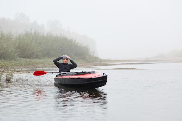 Junger kajakfahrer, der in seinem kanu aufwirft und hände auf kopf hält