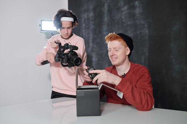 Junger kameramann, der glücklichen männlichen vlogger schießt, der neue fotokamera über offener box hält, während er durch schreibtisch sitzt