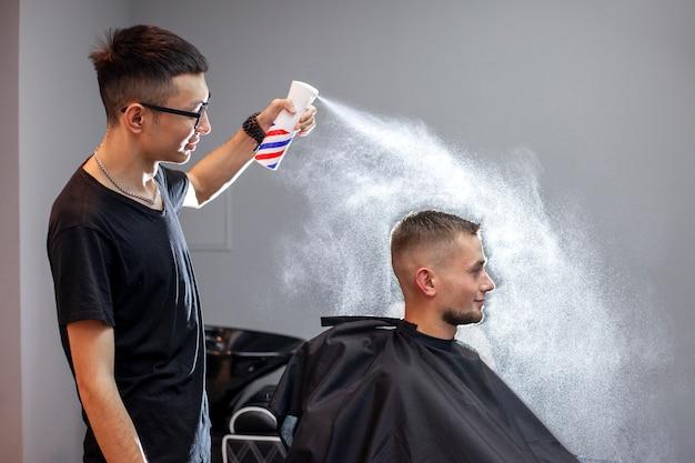Junger kasachischer friseur arbeitet in einem friseursalon, ein junger mann macht einen kurzen haarschnitt bei einem friseur, macht sich nass, wasser spritzt auf einem grauen wandhintergrund