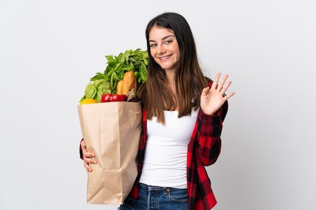 Junger kaukasier mit gemüse lokalisiert auf weißem gruß mit hand mit glücklichem ausdruck