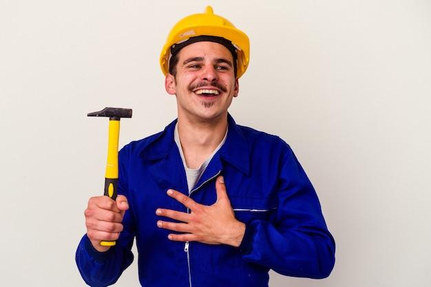 Junger kaukasischer arbeiter, der einen auf weißem hintergrund isolierten hammer hält, lacht laut und hält die hand auf der brust.