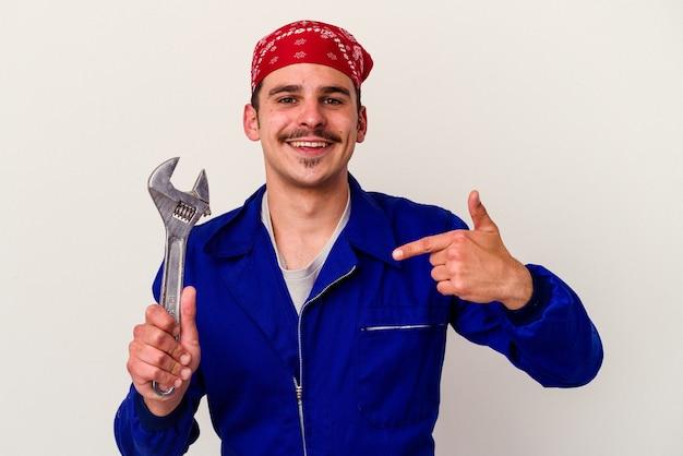 Junger kaukasischer arbeiter, der einen schraubenschlüssel einzeln auf weißem hintergrund hält, der mit der hand auf einen hemdkopierraum zeigt, stolz und selbstbewusst