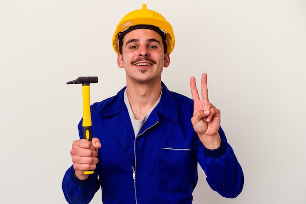 Junger kaukasischer arbeitermann, der einen hammer lokalisiert auf weißem hintergrund hält, der nummer zwei mit den fingern zeigt.