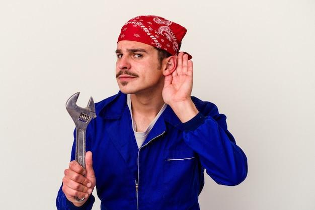 Junger kaukasischer arbeitermann, der einen schraubenschlüssel hält, der auf weißem hintergrund lokalisiert wird, der versucht, einen klatsch zu hören.