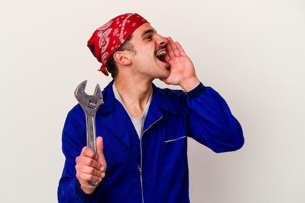 Junger kaukasischer arbeitermann, der einen schraubenschlüssel hält, der auf weißem hintergrund lokalisiert wird, schreit und hält palme nahe geöffnetem mund.